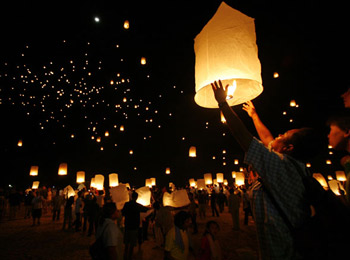 Floating paper lanterns fill the sky over the Andaman Sea in remembrance of the Indian Ocean tsunami victims. Image source: Reuters/Chaiwat Subprasom